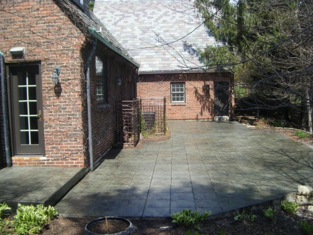 Backyard patio using gray 16x16 inch tile stamped concrete.