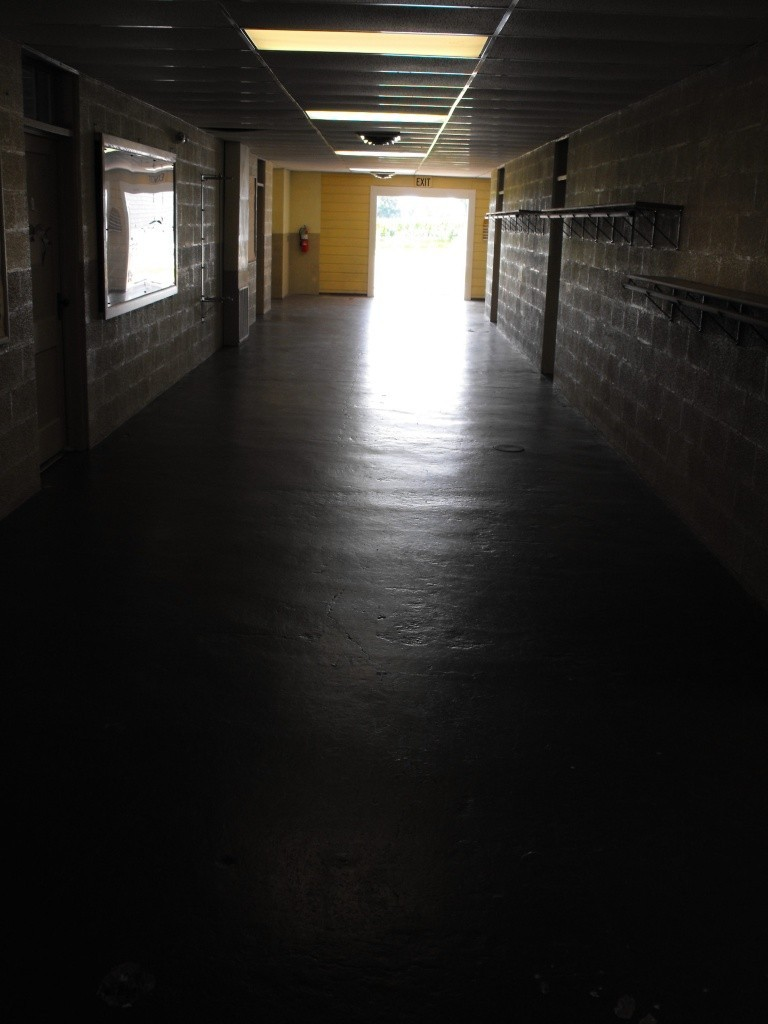A dark hallway with mottled, pitted floor.