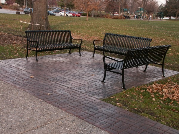 Three iron benches sitting atop some stamped concrete made to look like red bricks.