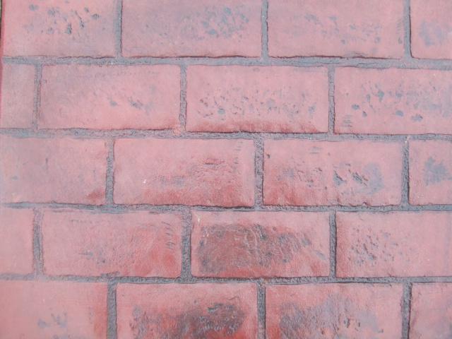 Closeup photo of a running bond brick concrete stamp.