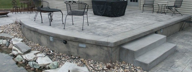 Gray Ashlar cut slate stamped concrete on a backyard patio.