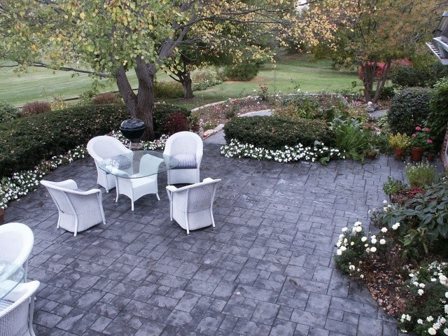 Ashlar cut stone stamped concrete in a backyard with white wicker chairs.