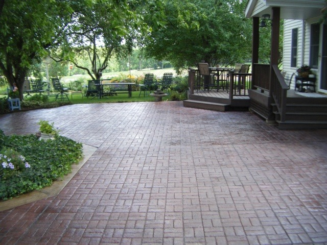 Basketweave pattern stamped concrete on a backyard patio in the shade.