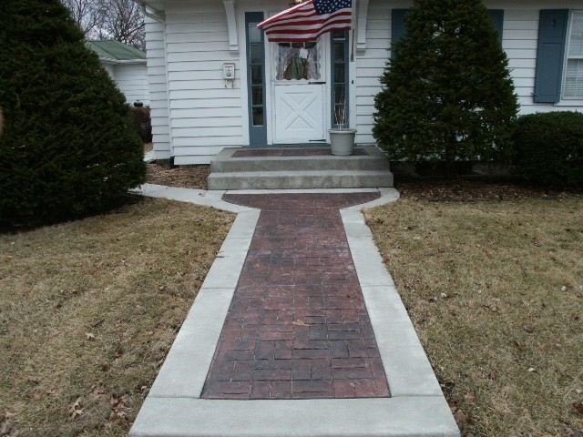Basketweave stamped concrete leading up to a white home with an American Flag up front.