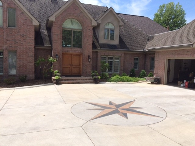 Colored concrete driveway with a decorative compass rose set in the center.
