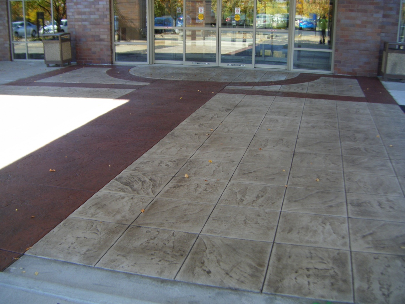 Commercial stamped concrete in front of a building with sliding glass doors.