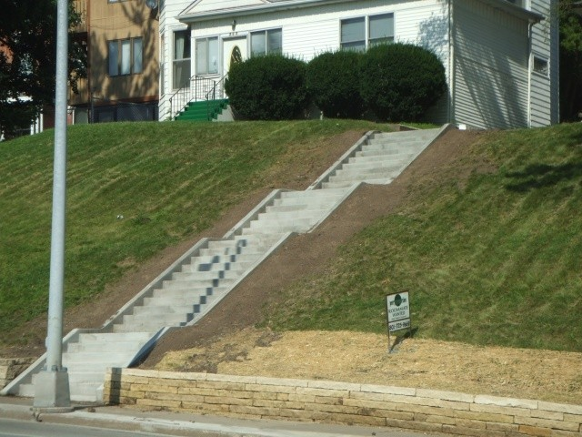 Three levels of concrete steps in front of a home