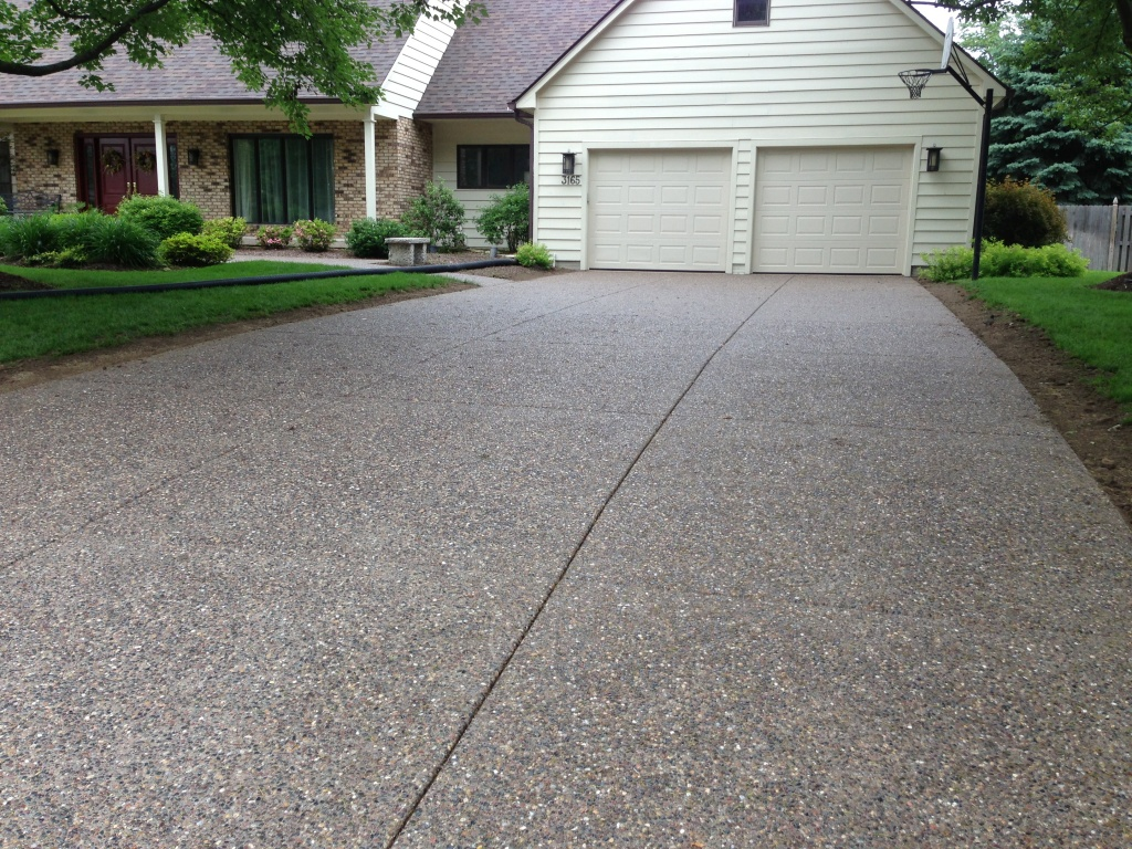 Exposed aggregate concrete driveway with tooled joints.