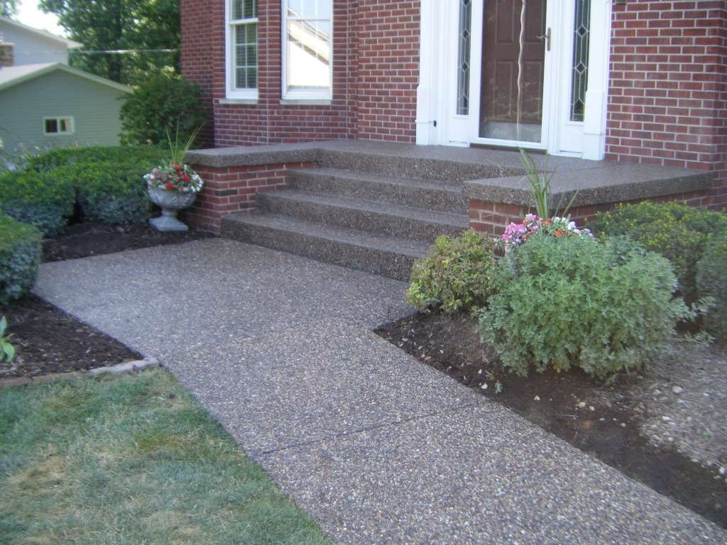Exposed aggregate concrete steps at a red brick home.