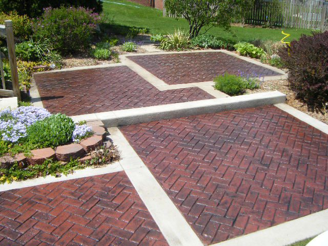 Harringbone brick stamped concrete in offset design in a backyard.
