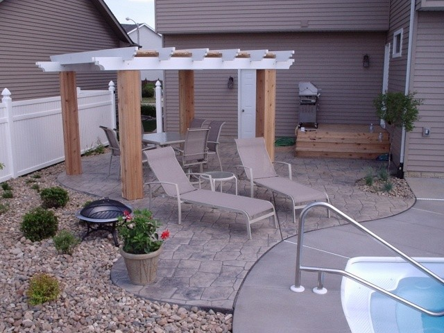 Luccia stone stamped concrete in a backyard with a pool and small pavilion.