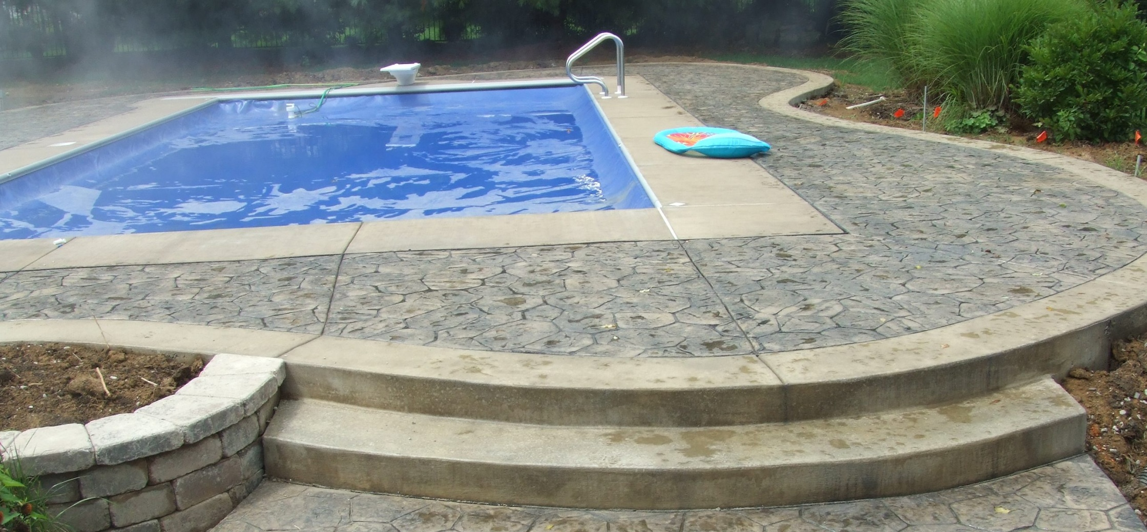 Random stone stamped concrete by a poolside.