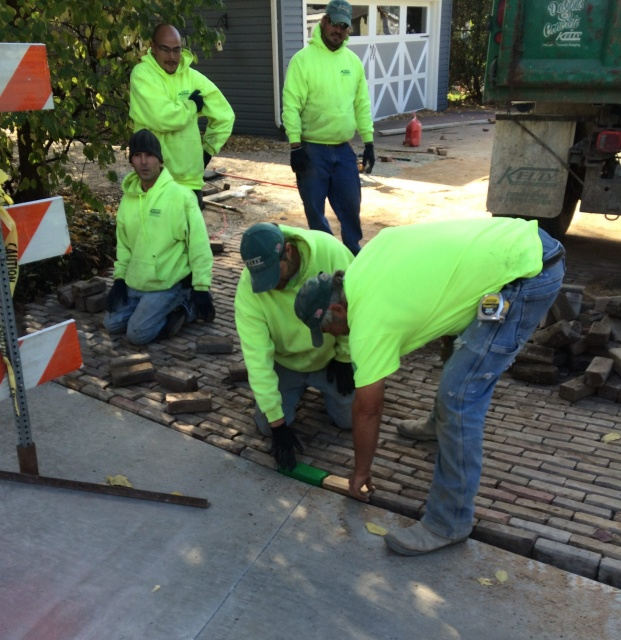 Two workers placing the last two bricks into a brick street