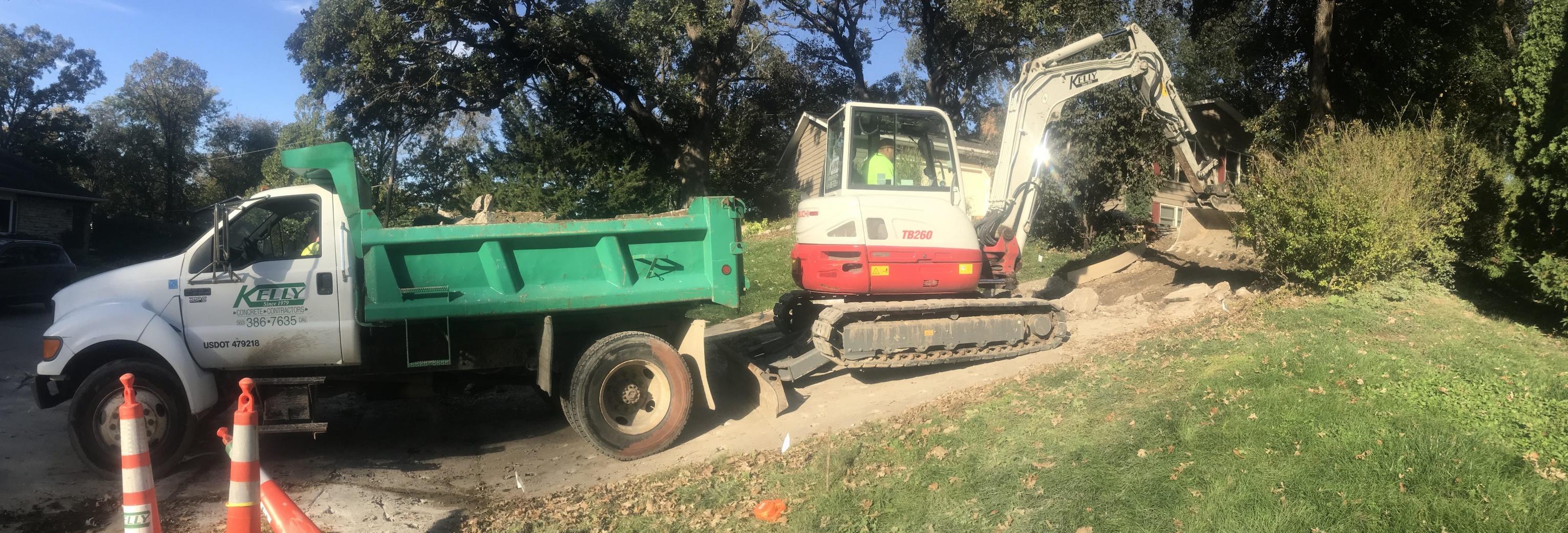 Excavator loading broken concrete into dump truck