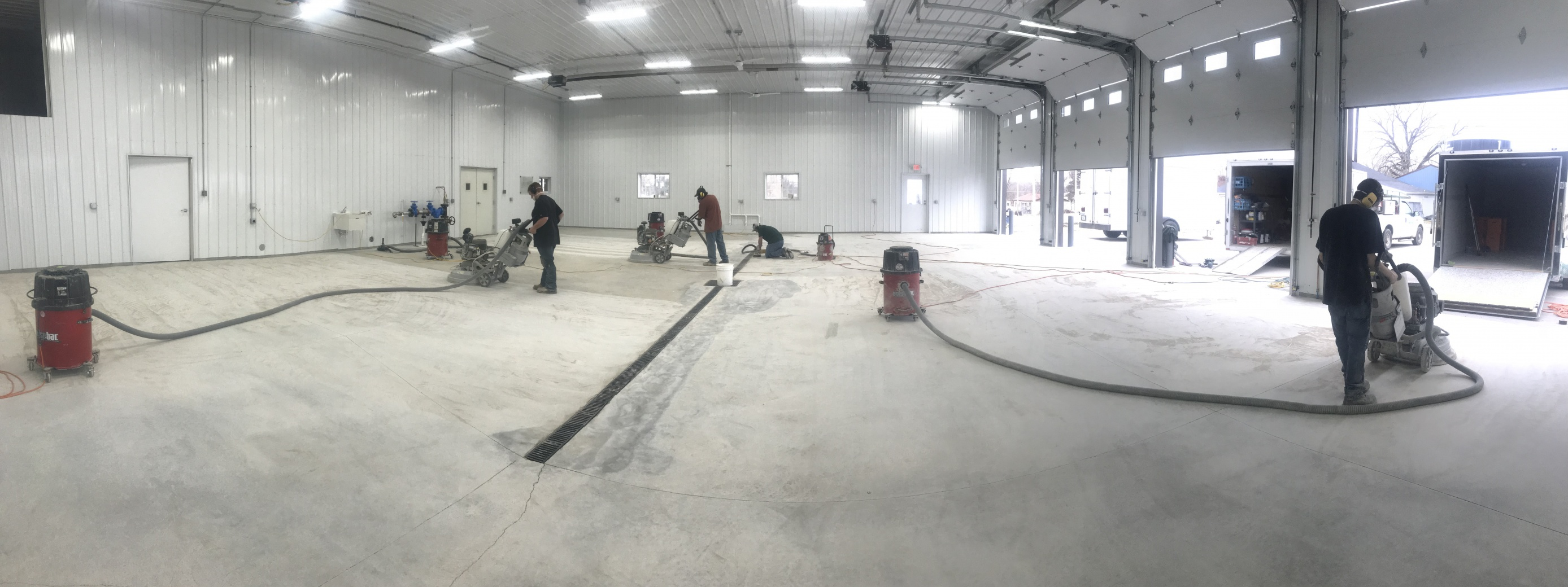 Concrete workers grinding concrete floor in large shop